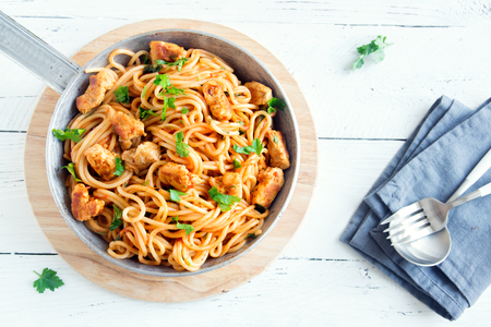 Spaghetti pasta in tomato sauce with chicken,  parsley in pan. Chicken spaghetti pasta over white wooden background with copy space, italian food.