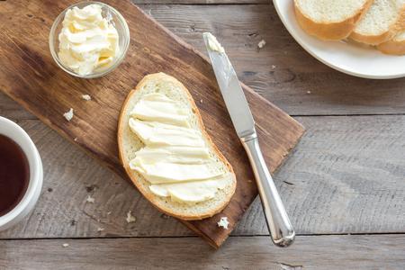 Burro e pane per la colazione, con una tazza di tè su fondo in legno rustico con spazio di copia. Colazione del mattino con tè, burro e toast.