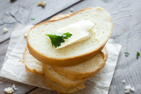 Butter and bread for breakfast, with parsley over rustic wooden background, top view