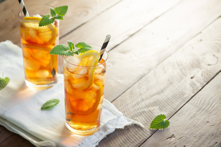 Iced tea with lemon, mint and ice cubes over wooden background, copy space. Iced cold summer drink.