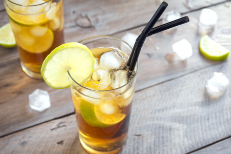 Iced Tea with lime and ice cubes over wooden background, copy space. Iced cold summer drink - Long Island Iced Tea Cocktail.