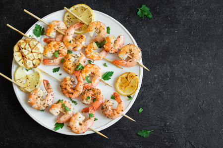 Grilled shrimp skewers. Seafood, shelfish. Shrimps Prawns skewers with spices and fresh herbs on stone black background, copy space. Shrimps prawns brochette kebab. Barbecue srimps prawns.