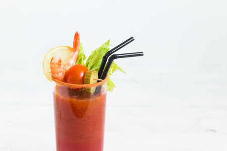 Bloody Mary Cocktail in glass with garnishes. Tomato Bloody Mary spicy drink on white background with copy space.
