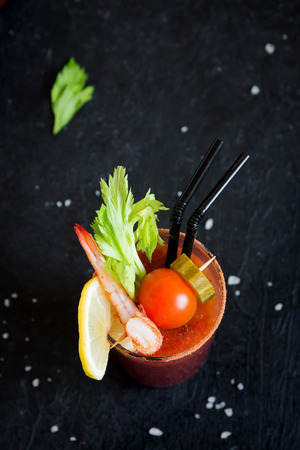 Bloody Mary Cocktail in glass with garnishes. Tomato Bloody Mary spicy drink on black background with copy space.