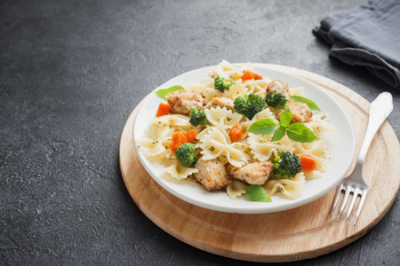 Farfalle pasta with chicken and vegetables. Pasta salad on black background, copy space. Banque d'images