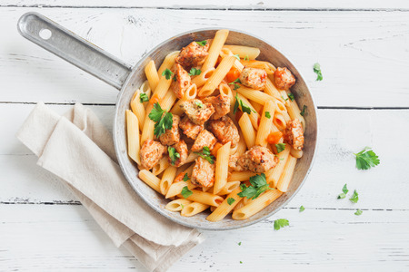 Penne pasta in tomato sauce with chicken,  parsley in pan. Chicken italian penne pasta over white background with copy space, italian food. Stock Photo