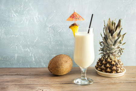 Pina Colada Cocktail with pineapple and coconut over wooden background, copy space. Summer tropical delicious cocktail.