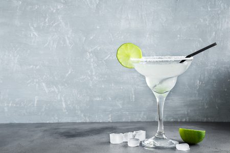 Cóctel Margarita con limón y hielo en la mesa de madera, espacio de copia.