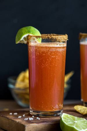 Michelada (Mexican Bloody Beer) with Spisy Rim and Tomato Juice served with Limes and Nacho Chips. Summer Alcohol Cocktail Michelada. Фото со стока