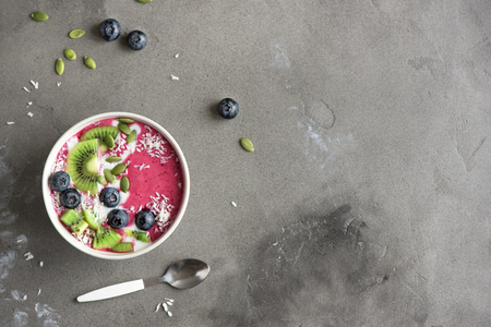 Smoothie bowl with fresh berries, fruits, seeds and coconut cream for healthy vegan vegetarian diet breakfast. Acai blueberry coconut smoothie bowl. Stock Photo