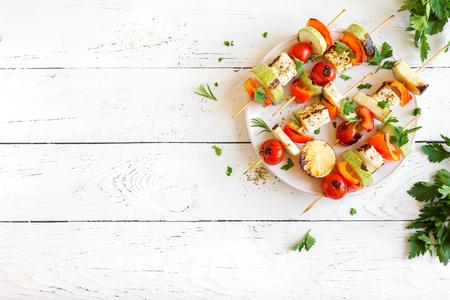 Vegetarisch grillen. Vegetarische spiesjes met halloumikaas en groenten op witte achtergrond, exemplaarruimte.