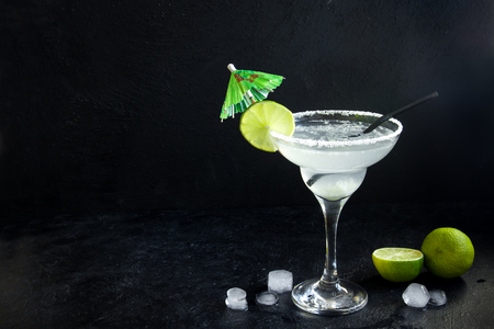 Margarita Сocktail with lime and ice on black stone background, copy space. Classic Margarita or Daiquiry Cocktail. Stock Photo