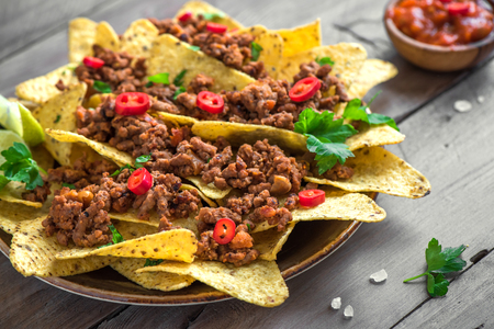 Mexican nacho corn tortilla chips with cheese, meat, guacamole and red hot spicy salsa. Nachos with ground beef on dark rustic background, copy space.