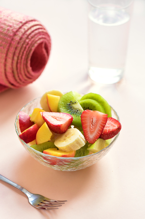 Sport and healthy lifestyle concept. Pink yoga mat and Fruit and Berries Salad in bowl for snack or breakfast on pink pastel background, copy space.