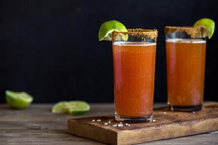 Michelada (bière mexicaine sanglante) avec Spisy Rim et jus de tomate servie avec limes et chips de nacho. Cocktail d'alcool d'été Michelada.