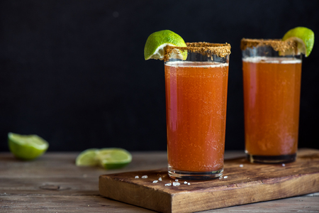 Michelada (Mexican Bloody Beer) with Spisy Rim and Tomato Juice served with Limes and Nacho Chips. Summer Alcohol Cocktail Michelada. Archivio Fotografico