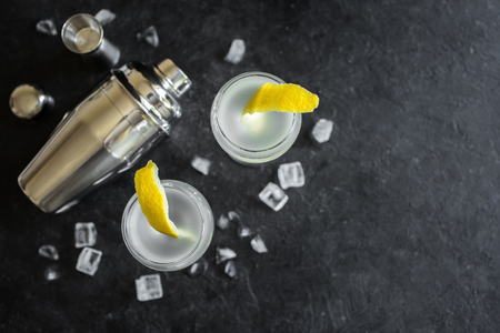 Alcohol Cocktail with lemon and ice. Gin tonic fizz or gimlet cocktail on black background, copy space. Banque d'images