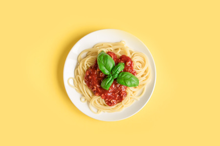 Spaghetti pasta bolognese on yellow background, top view. Plate of pasta dish with tomato sauce and basil on creative yellow background.