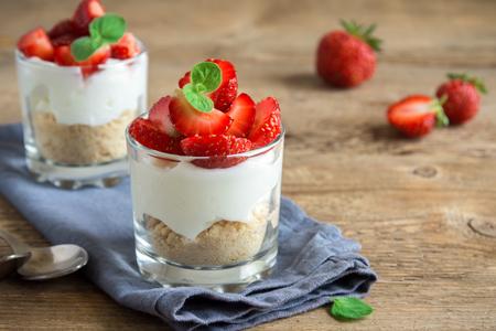 Erdbeer-Kleinigkeiten-Mini-Dessert in Gläsern mit frischen Erdbeeren und Frischkäse auf hölzernem Hintergrund. Gesundes hausgemachtes Trankdessert.
