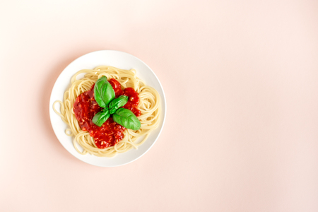 Spaghetti pasta bolognese on pink pastel background, top view. Plate of pasta dish with tomato sauce and basil on creative pink background. Banque d'images