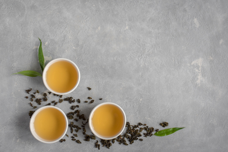Green tea in ceramic cups, dry green oolong tea and tea leaves on grey stone table, top view, copy space.