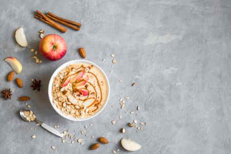Appeltaart Smoothie Bowl. Ontbijt smoothie kom met appels, kaneel, amandelmelk, havergranola, gezouten karamel en kruiden, bovenaanzicht, kopie ruimte. Stockfoto