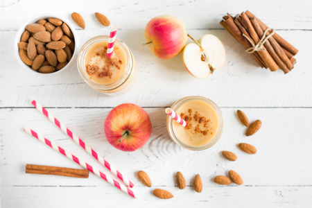 Apple pie protein smoothie drink with almond milk. Homemade apple smoothie with apple pie spices (cinnamon) on white wooden background, copy space.