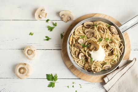 白い背景にキノコスパゲッティパスタとクリームソース、トップビュー。調理鍋にシャンピニオンマッシュルームと自家製イタリアのパスタ。