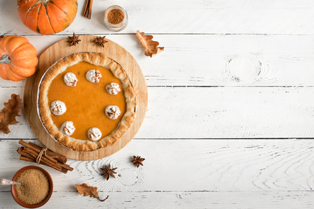 Pumpkin Pie with whipped cream and cinnamon on white wooden background, top view. Homemade pastry for Thanksgiving traditional Pumpkin Pie.