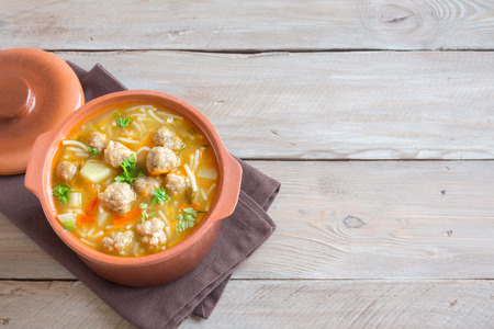 Meatball soup with vegetables and noodles over wooden background with copy space. Homemade meatball soup.