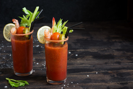 Bloody Mary Cocktail in glasses with garnishes. Tomato Bloody Mary spicy drink on dark wooden background with copy space.