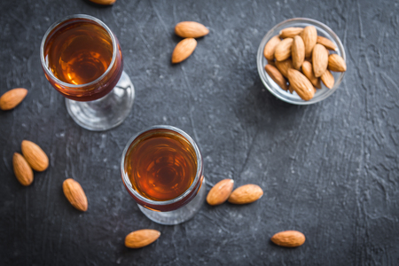 Italian liqueur Amaretto with almonds on black stone background, top view