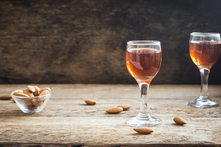 Italian liqueur Amaretto with almonds on rustic wooden background, copy space