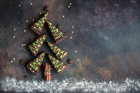 Chocolate Brownies in shape of Christmas Tree with green icing and festive sprinkles, top view, copy space. Sweet Christmas or winter holidays pastry food concept. Archivio Fotografico