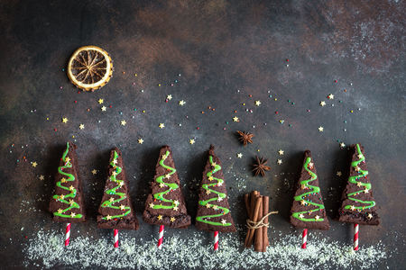 Chocolate Brownies in shape of Christmas Trees with green icing and festive sprinkles, top view, copy space. Sweet Christmas or winter holidays pastry food concept. Zdjęcie Seryjne - 110037618