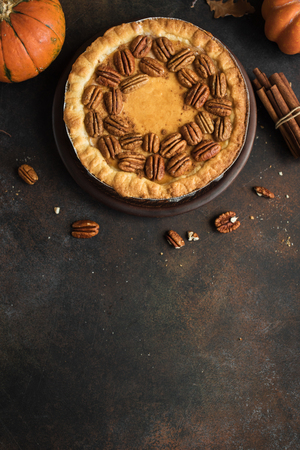 Pumpkin and Pecan Pie with cinnamon on rustic background, top view, copy space. Homemade autumn pastry for Thanksgiving.