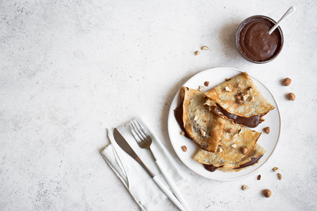 Crepes with chocolate and hazelnuts. Homemade thin crepes for breakfast or dessert on white, copy space.