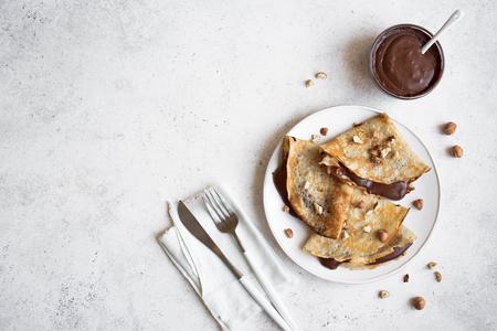 Naleśniki z czekoladą i orzechami laskowymi. Domowe cienkie naleśniki na śniadanie lub deser na białym, kopia przestrzeń.