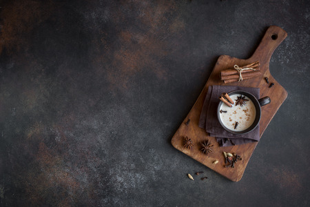 Traditional indian masala chai tea in ceramic cup with ingredients. Spicy black tea with milk on rustic dark background, copy space.