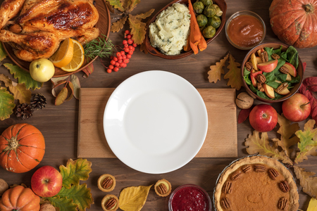 Thanksgiving dinner background with turkey and all sides dishes, pumpkin pie, fall leaves and seasonal decor around white plate, top view, copy space. 版權商用圖片
