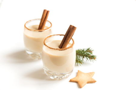Eggnog with cinnamon and nutmeg for Christmas and winter holidays. Christmas Eggnog, gingerbread cookies isolated on white background. 写真素材
