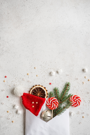 Christmas composition with sweets, fir branch, ornaments and envelop, flat lay on white, copy space. Christmas greeting card, design, concept. Stock Photo