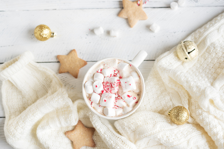 Christmas Hot chocolate with marshmallows, peppermint candies in white mug, top view. Hot cocoa drink for Christmas and winter holidays with warm scarf, festive decor.