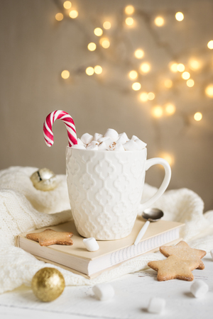 Christmas Hot chocolate with marshmallows, peppermint candy cane in white mug, copy space. Hot cocoa drink for Christmas and winter holidays with lights and festive decor.