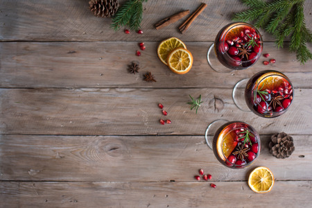 Christmas sangria or Mulled wine with oranges, pomegranate seeds, cranberry, rosemary and spices - homemade festive drink for Christmas time.
