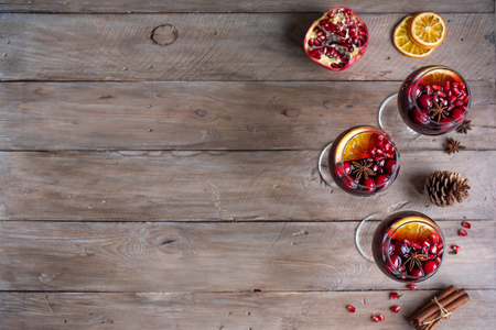 Red Sangria with oranges, pomegranate seeds, cranberry, rosemary and spices - homemade festive autumn or winter drink mulled wine, sangria. Stock Photo