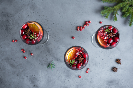 Red Sangria with oranges, pomegranate seeds, cranberry, rosemary and spices - homemade festive drink mulled wine for Christmas time. Stock Photo