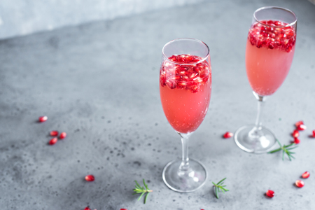 Pomegranate Champagne Mimosa Cocktail (Mocktail) with rosemary on concrete background, copy space. Mimosa Drink for Valentine Day or other holidays. Archivio Fotografico