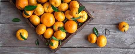 Tangerines (oranges, clementines, citrus fruits) with green leaves in box on wooden background, top view, banner.