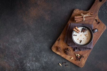 Traditional indian masala chai tea in ceramic cup with ingredients. Spicy black tea with milk (Masala) on rustic dark background, copy space.